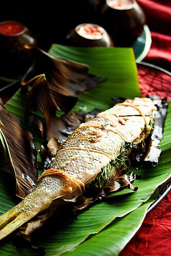 A grilled whole fish on a banana leaf