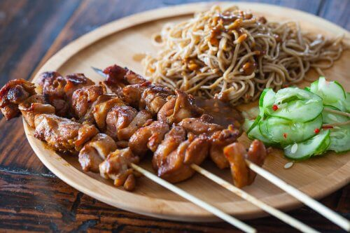 chicken satay and noodles on a wooden plate