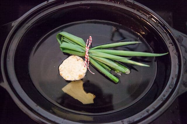 Slow Cooker Bone Broth Recipe - Asian Tie green onions with twine and slice ginger in half