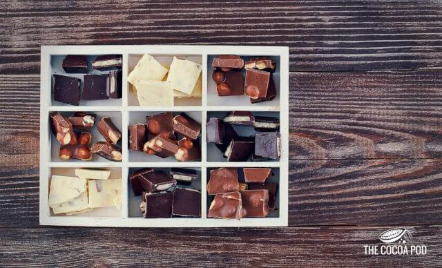 Wooden box with set of dark, white and milk chocolate on wooden