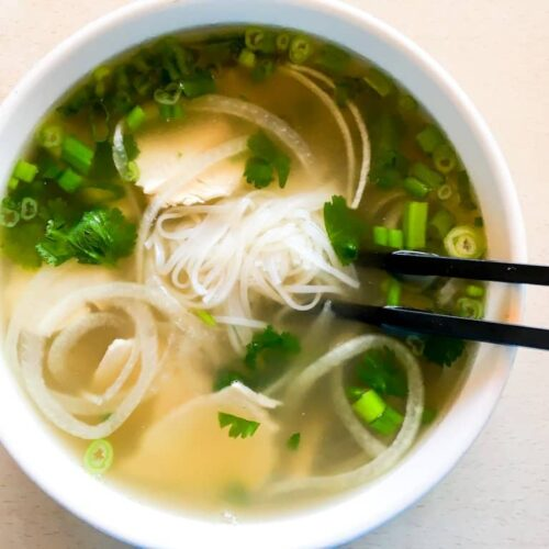 chicken pho in a white bowl with chopsticks
