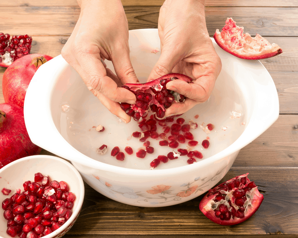 removing pomegranate seeds in bowl of water