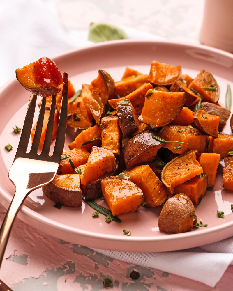 diced sweet potatoes on a pink plate with herbs.