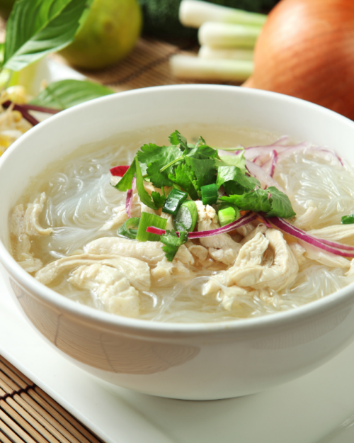 noodle soup in a white bowl with shredded chicken and herbs.