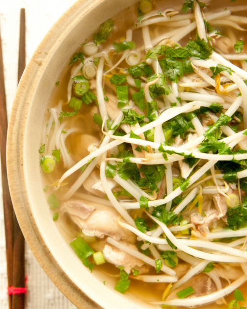 Up close photo of chicken pho topped with bean sprouts and herbs.