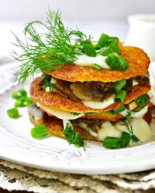 stacked potato pancakes with a burger sandwiched inside.
