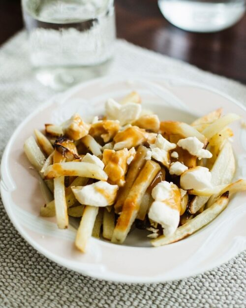 french fry poutine covered in gravy on a white plate.