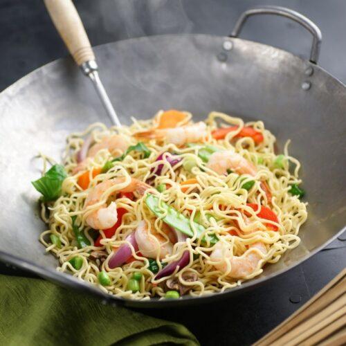 shrimp noodle dish in a wok.