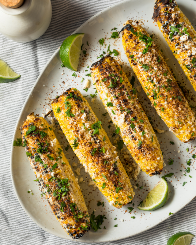4 Elote-style corn on the cobs, grilled with herbs and cotija cheese on a white plate.