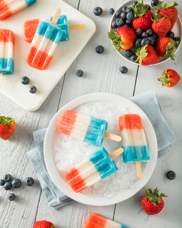 Red, white, and blue popsicles on a bed of ice next to a bowl of strawberries and blueberries.