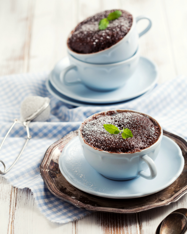 two chocolate cakes in blue mugs.