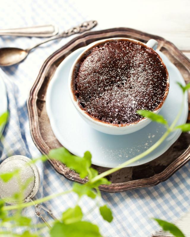 overhead shot of chocolate mug cake on a blue plate and plaid napkin.
