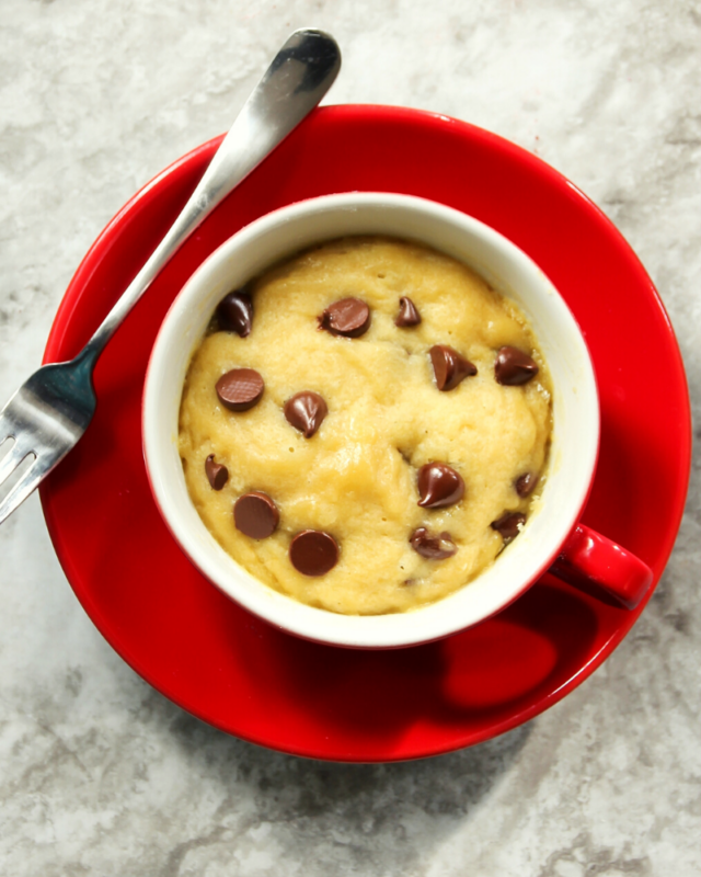 chooclate chip cookie in a mug on a red plate with a fork.