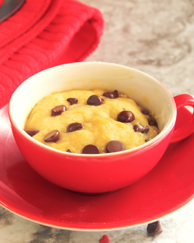 Up Close photo of a chocolate chip cookie in a red mug with chocolate chips on top.