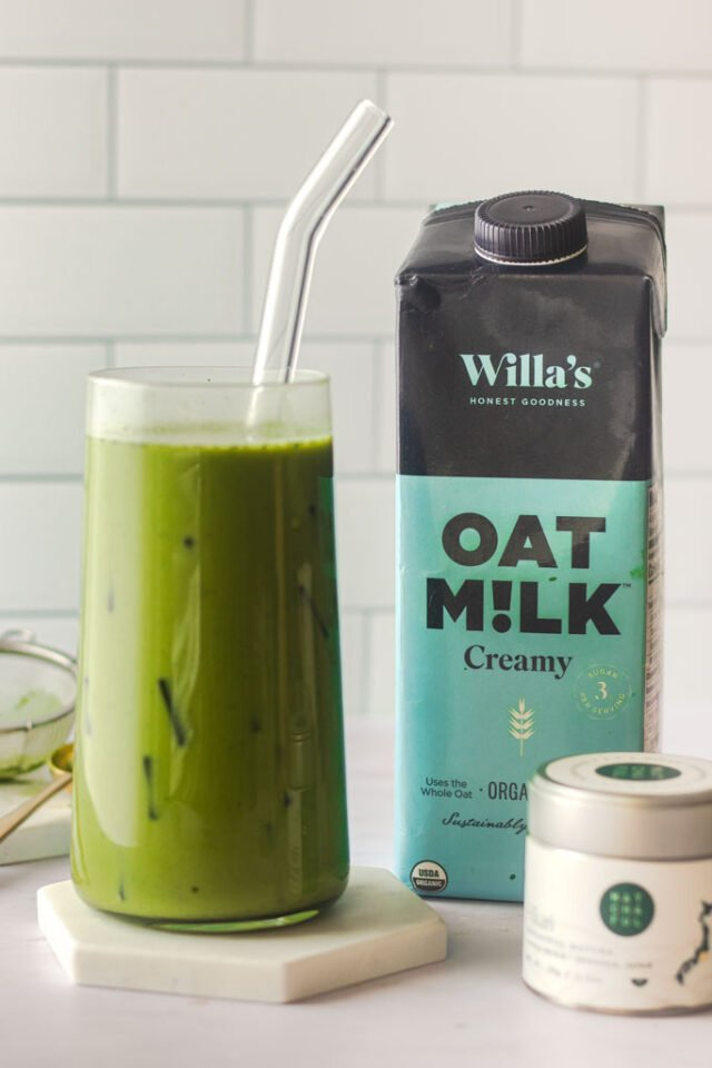 Green tea latte over ice next to a bottle of oat milk.