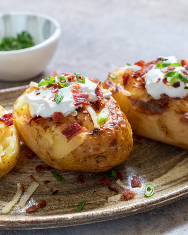 baked potato topped with sour cream and bacon.