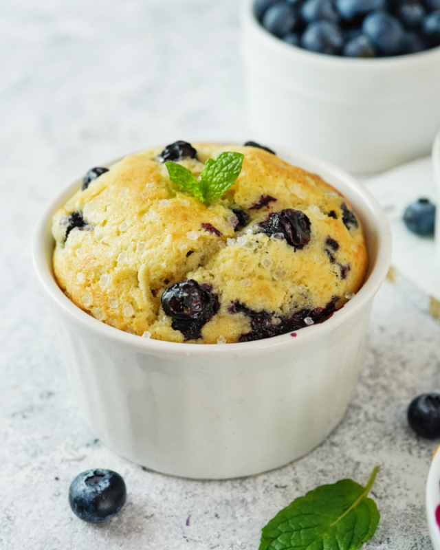 blueberry mug cake in a white dish next to fresh blueberries.