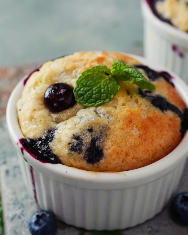 Blueberry mug cake with fresh blueberries bursting and a mint leaf.