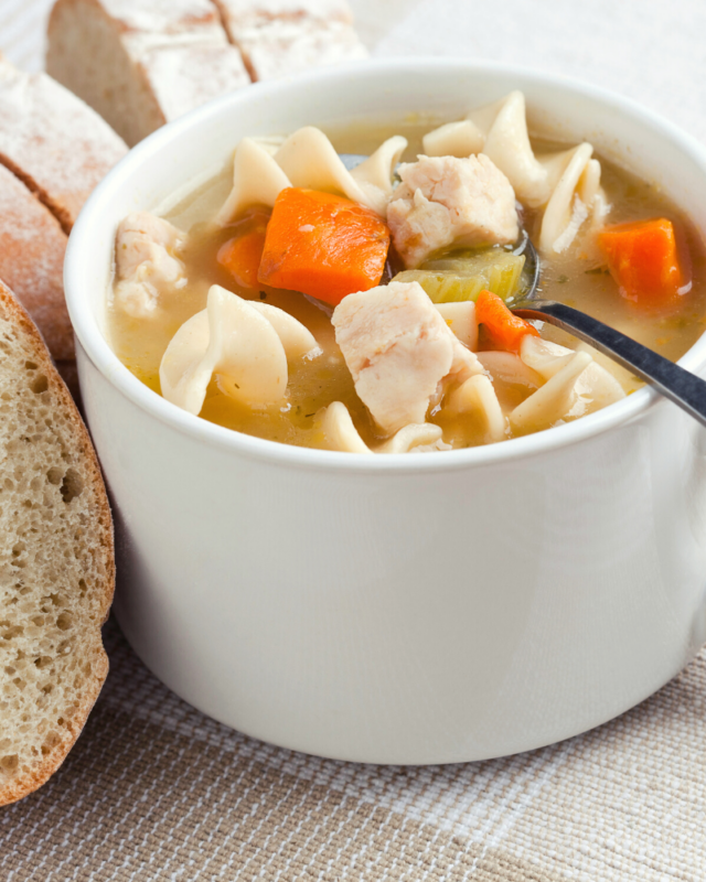 Chicken noodle soup in a white mug with toasted bread.