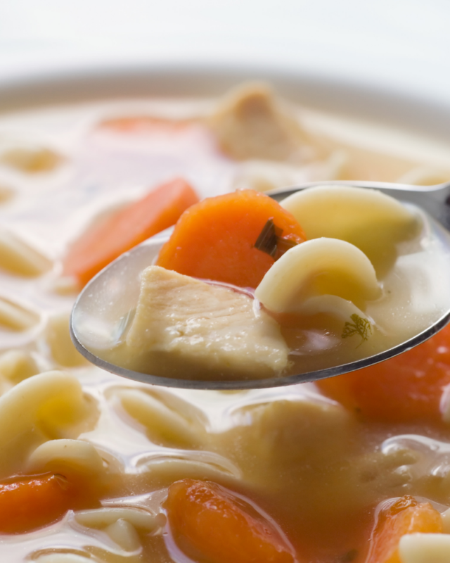 Chicken soup on a spoon with noodles, carrots, and broth.