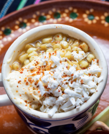 elote corn in a mug on a red plate.