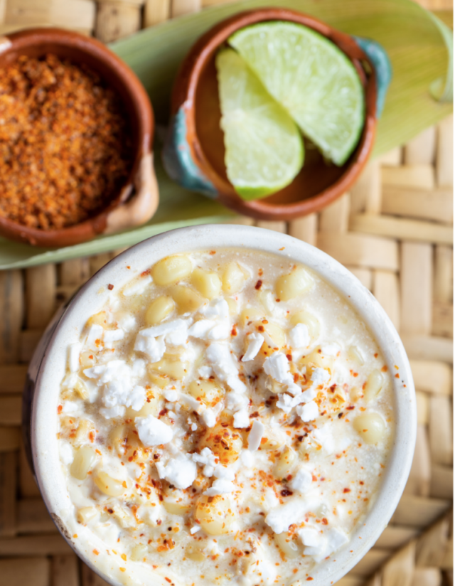 creamy elote in a white mug with limes.