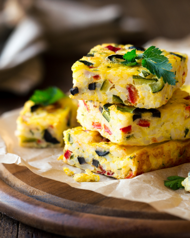 vegetable frittata slices stacked on parchment paper.