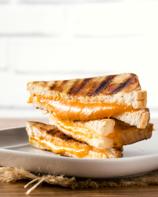 grilled cheese stacked on a white plate.