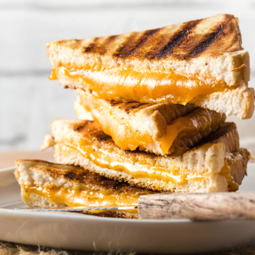 Stack f 4 grilled cheese sanwiches with orange cheddar cheese oozing out of the middle.