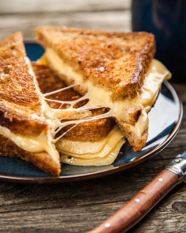 Grilled cheese halves being pulled apart on a black plate.