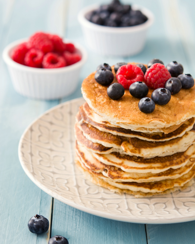 Pancakes stacked with fresh blueberries and raspbaerries.