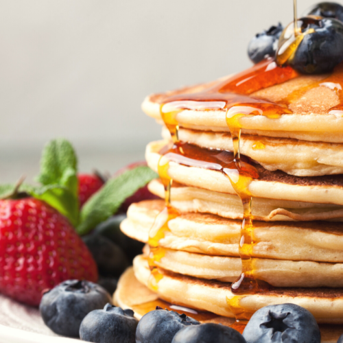 stacked pancakes dripping with maple syrup.