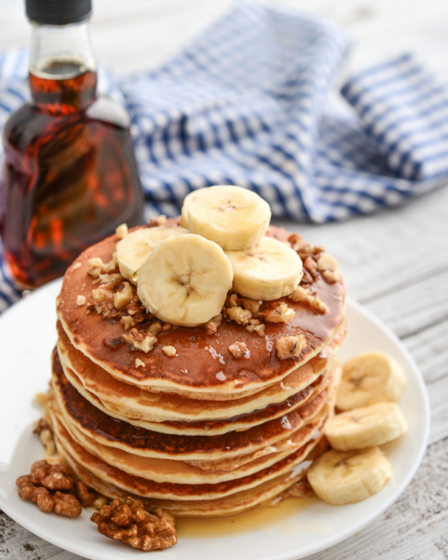 Pancakes stacked with bananas and walnuts on a white plate.