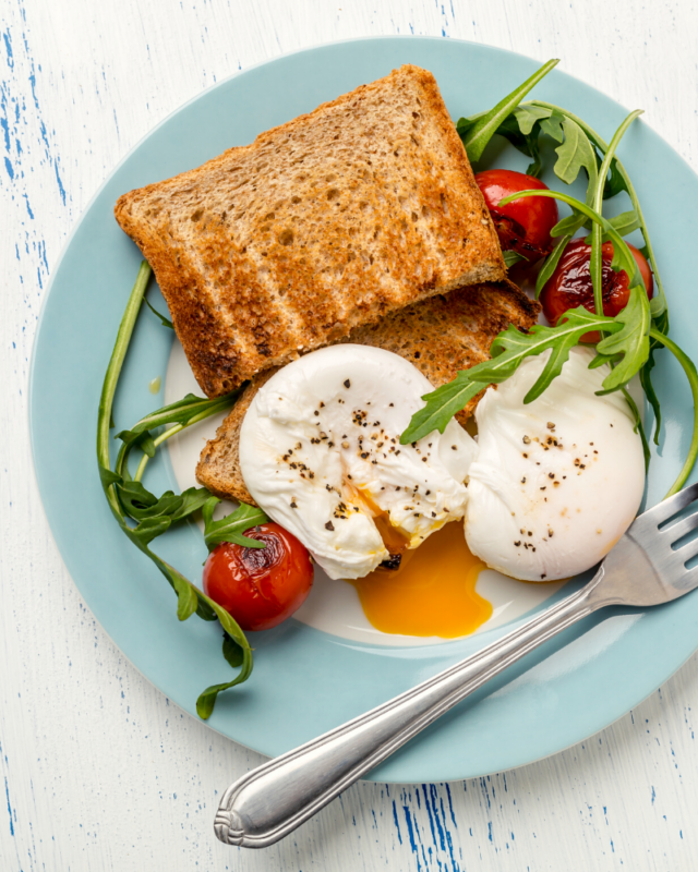 two poached eggs with a salad on a blue plate.