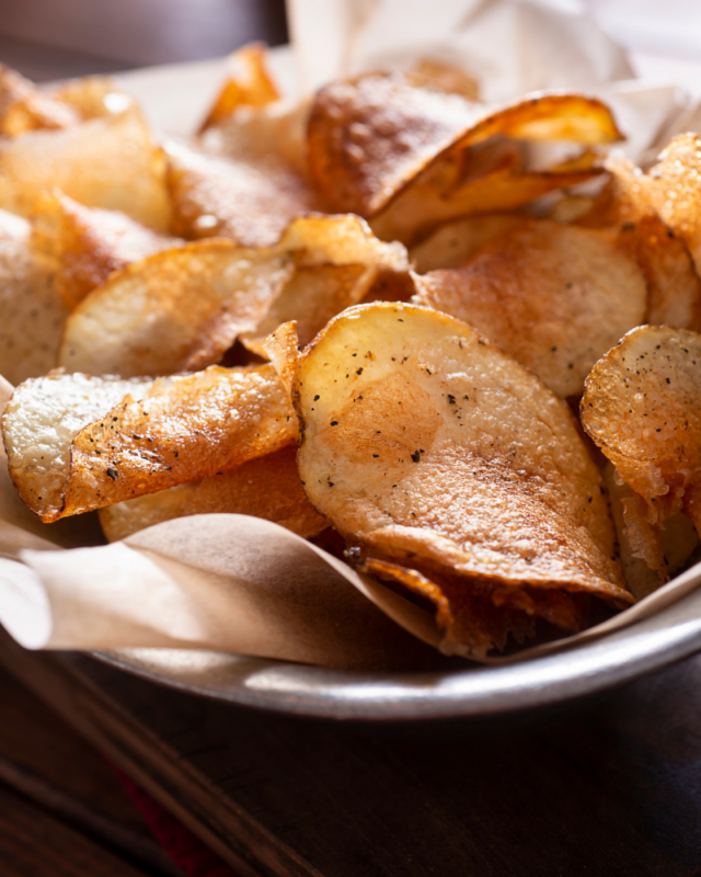Potato chips on parchment paper in a big bowl.