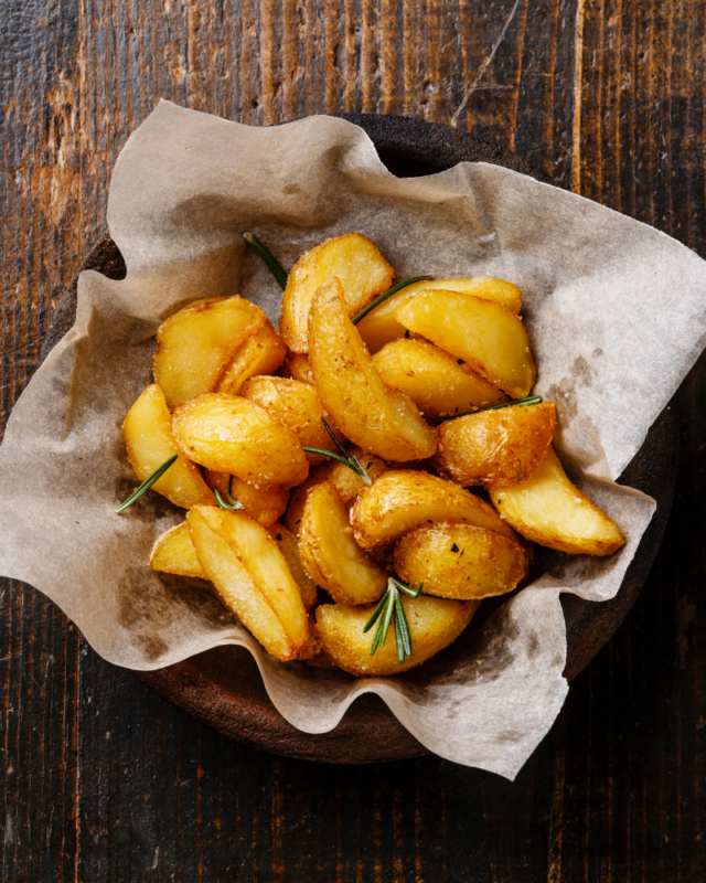 potato wedges with fresh rsemary on white parchment paper.