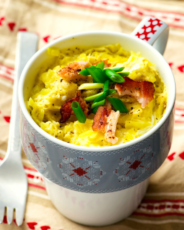 Bacon and egg quiche in a blue and white mug with scallions.