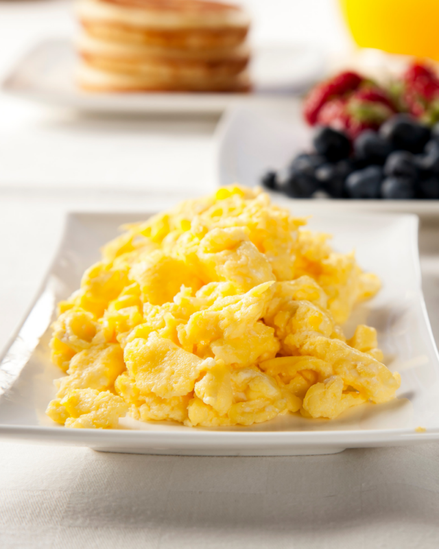 scrambled eggs on a white plate with berries.