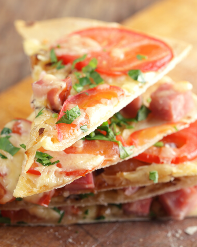 Slices of tortilla pizza with ham and fresh tomatoes stacked.